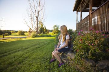 Thoughtful schoolgirl sitting on stones at yard
