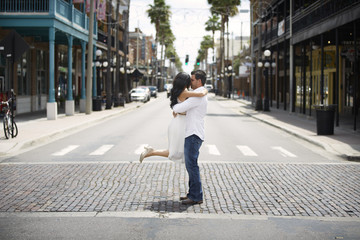 Romantic couple kissing while standing on city street