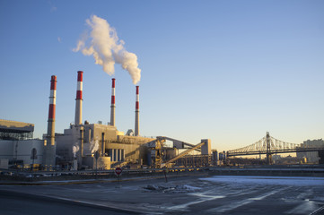Smoke Stacks in factory by bridge against clear sky