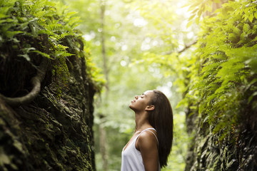 Side view of woman with eyes closed standing in forest