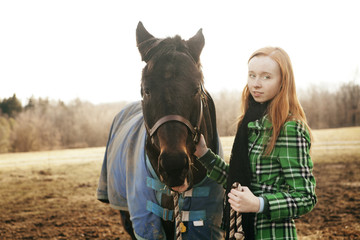 Portrait of teenage girl with horse standing on field against clear sky