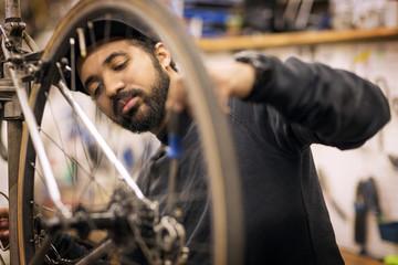 Man repairing bicycle while working in workshop
