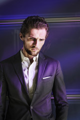 Purple lights falling on thoughtful businessman standing against glass wall