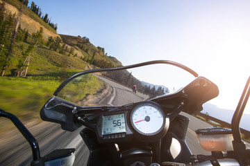 Cropped image of motorcycle moving on mountain road against clear sky