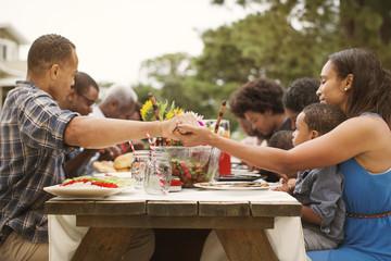 Family praying before meal in backyard