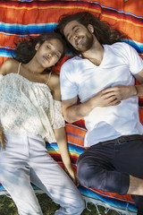 High angle view of couple lying on blanket at park