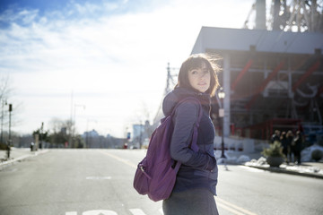 Woman with hand in pocket looking away while standing on road
