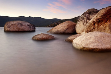 Scenic view of boulder rocks in sea during sunset