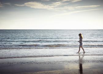 Girl walking along beach
