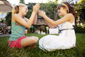 Girls playing while sitting on grassy field in yard