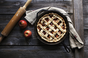 Close up of apple tart served in frying pan on wooden table