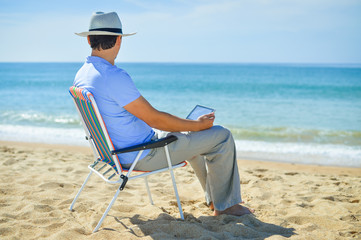 Man using tablet relaxing on ocean beach, blue sky outdoors background