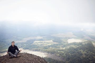 Man meditating in mountains