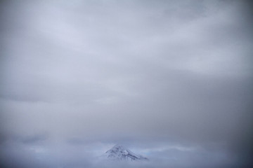 Foggy clouds above snowy mountain peak