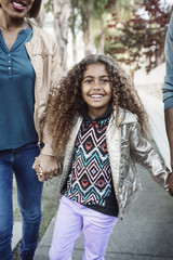 Girl holding hands with parents on sidewalk