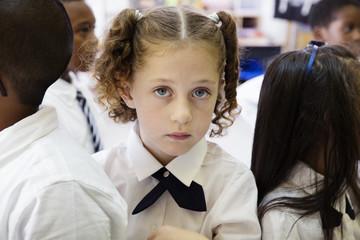 Portrait of schoolgirl standing with classmates in classroom