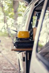 Saucepan standing on camping stove in mini van