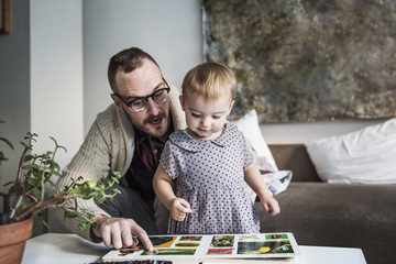 Father and daughter looking at book while sitting on sofa