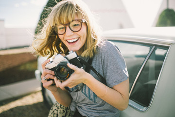 Outdoor portrait of young woman holding camera