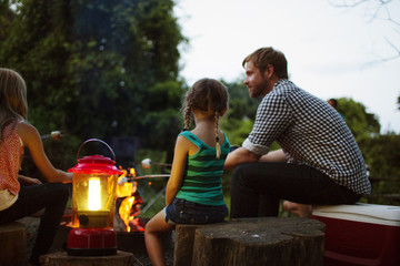 Father and daughters sitting by lantern roasting marshmallows at summer camp