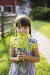 Portrait of girl holding fennel while standing on field