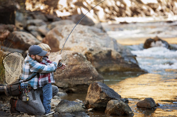 Father and son fishing in river