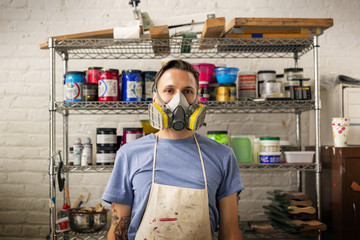 Portrait of worker wearing protective mask standing in workshop