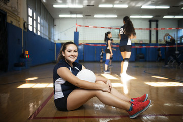 Portrait of teenage girl sitting in volleyball court