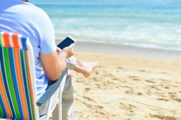 Person chilling on beach talking using smartphone. Back side view of guy enjoying outdoors background