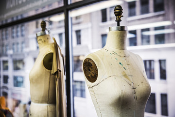Dressmaker's models by glass window at design studio
