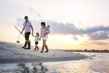 Full length of family walking on seashore against sky during sunset