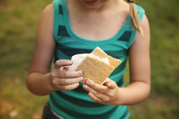 Midsection of girl holding smores at summer camp
