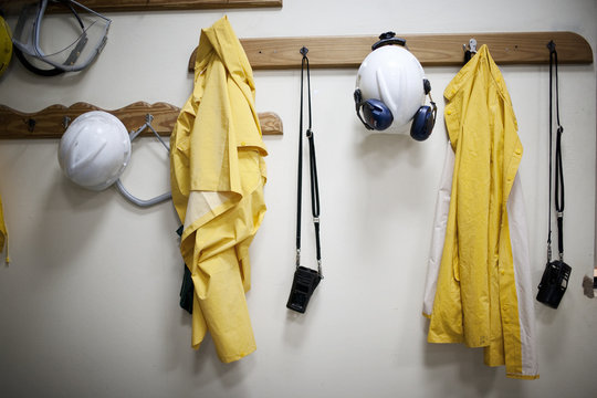 Protective workwear hanging from coat hooks