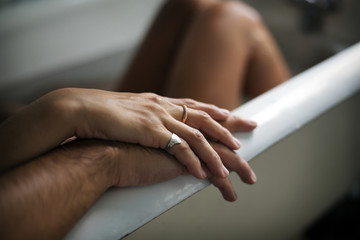 Close up of couple hands on bathtub