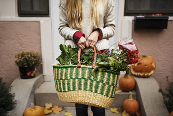 Midsection of woman holding vegetable and flower basket