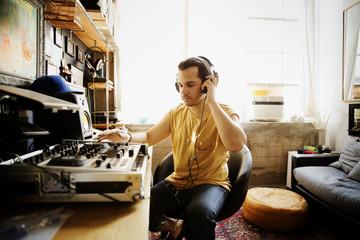 Serious DJ playing sound mixer at recording studio