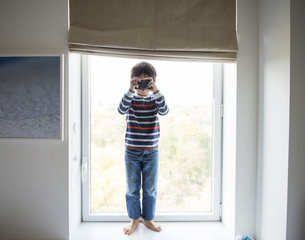 Boy taking a photo with camera while standing on window sill
