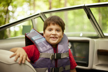 Portrait of happy boy wearing life jacket sitting at boat in forest