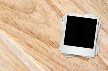 Blank polaroid photo papers on wooden background.