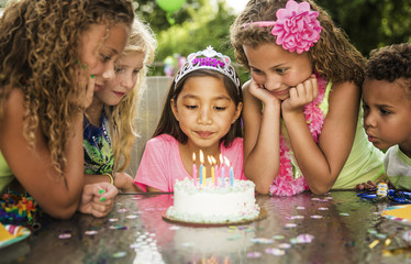 Excited children looking at birthday cake on table in backyard