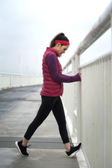 Young woman exercising on bridge