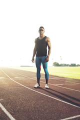 Sportsman standing on running track in sunny day
