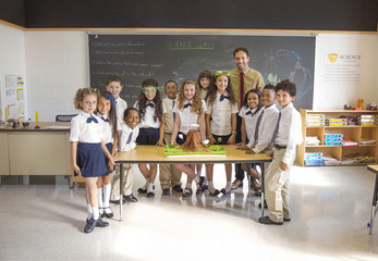 Portrait of students with teacher standing at desk in classroom
