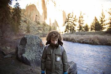 Boy in winter jacket by river