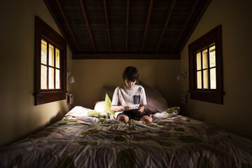 Boy using digital tablet while sitting on bed