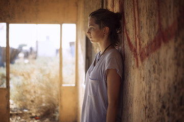 Thoughtful woman standing against wall in abandoned house