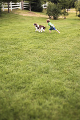 Boy running with dog on grass in backyard