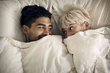 Young couple lying in bed under blanket