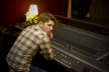 Thoughtful man leaning on sound mixer in recording studio
