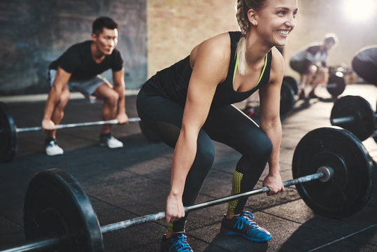Woman performing dead lift barbell exercise